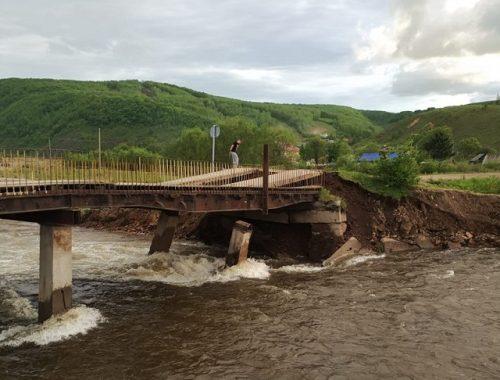 Потоки воды размыли опору моста в Облучье: часть города отрезана